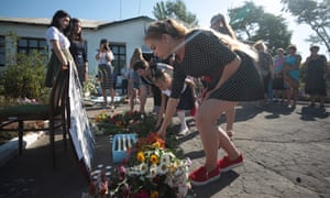 Local villagers lay flowers near pictures of the passengers on flight MH17 flight at a makeshift memorial in Petropavlivka village in eastern Ukraine on Sunday.