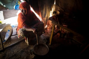 A woman stirs a pot of porridge next to her children at their shelter in a camp for displaced people in Mogadishu