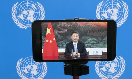 Chinese President Xi Jinping is seen on a phone screen remotely addressing the 75th session of the United Nations General Assembly