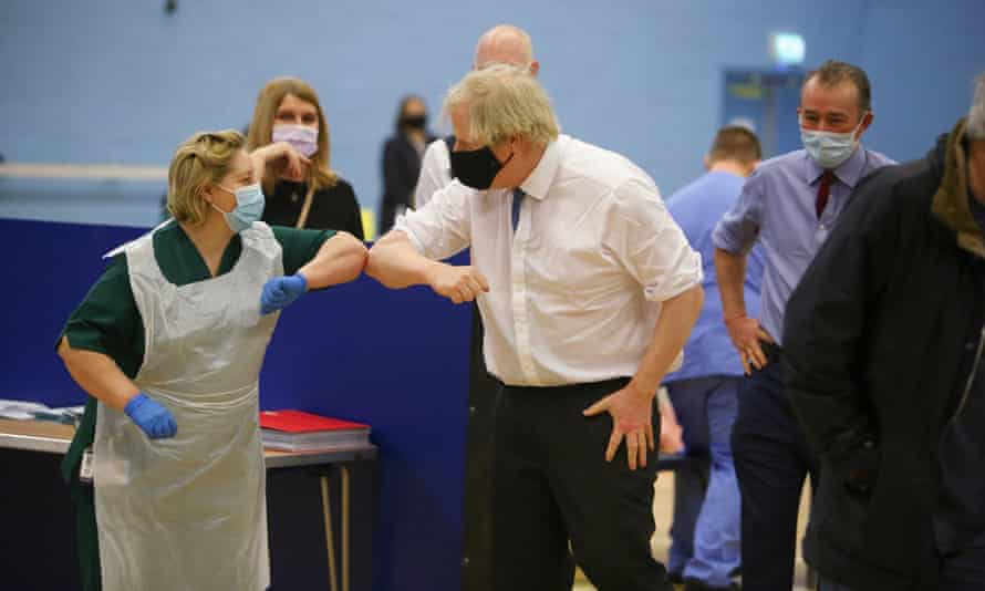 Boris Johnson touches elbows with a nurse during a visit to a vaccination centre in Cwmbran, south Wales.