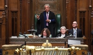 In House of Commons, gold mace in foreground out of focus, Bercow stands with three others sitting around.