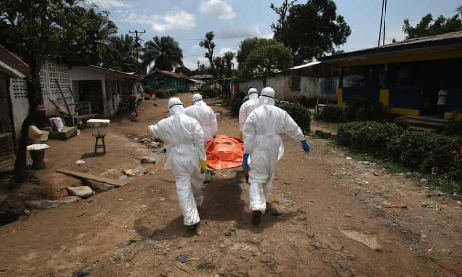 An Ebola burial team carries the body of a woman through a suburb of Monrovia, Liberia.