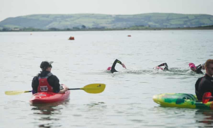 Swimmers in water near Aberdovey, Wales, UK.