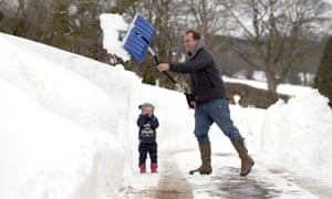Father and daughter clear the snow