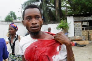 An injured opposition supporter outside the headquarters of the UDPS