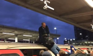 A furious commuter drags an Extinction Rebellion protester off the roof of a Tube train at Canning Town last week.