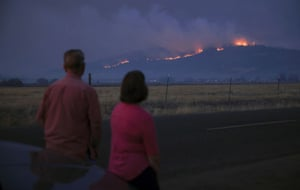 Local residents look at smoke and fire over a hill during wildfires near the town of Medford, Oregon, U.S. September 9, 2020.