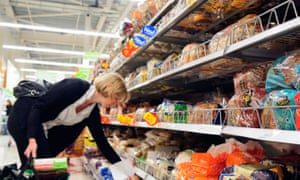 Woman buying bread in an Asda supermarket