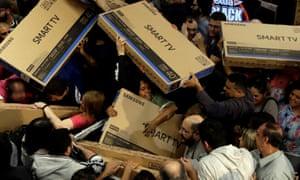 Black Friday shoppers grab TVs in Brazil.