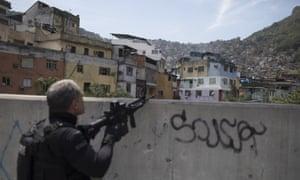A police officer takes a position during an operation in the Rocinha favela in Rio de Janeiro, Brazil Friday.