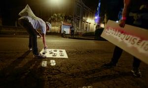 Una cicli-activista en San José pinta una hilera de huellas de pies atravesando la calle, creando un paso peatonal.