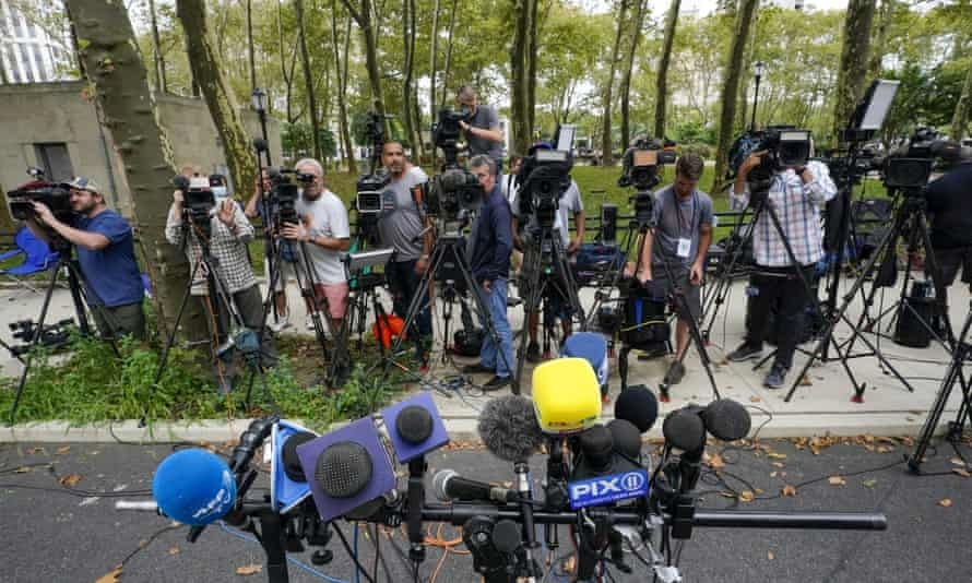 Television crews wait for lawyers to come speak to the media during a break in the trial.