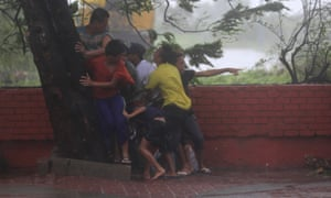 People take cover under a tree after strong winds brought by typhoon Rammasun, locally called Glenda, battered Manila, the Philippines, in July 2014.