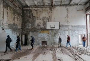 Tourists visit an abandoned gymnasium in Pripyat