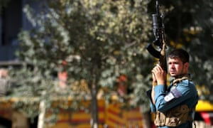 An Afghan security official holds a rifle in the air, Kabul