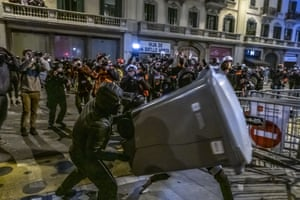 A protester throws a rubbish bin at police in Barcelona. Shops in the city centre were targeted and windows broken