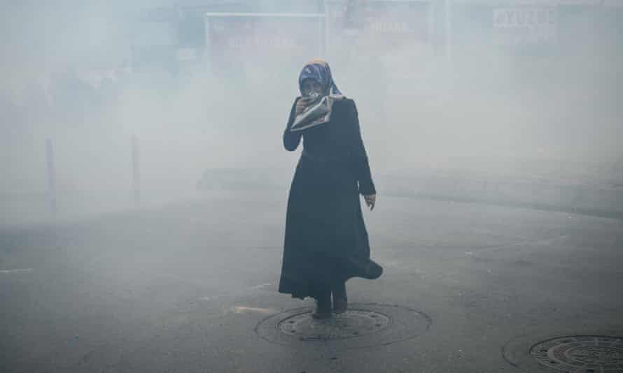 A woman covers her face against tear gas
