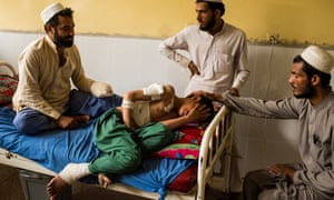 Family members comfort a 12-year-old boy who was injured in a US drone strike in Nangarhar province.