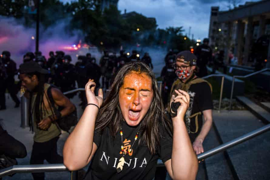 A woman reacts after being sprayed by pepper spray next to the Colorado State Capitol in Denver.