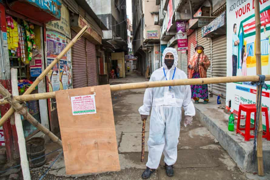 A man in a white protective suit guards a closed-off alleyway