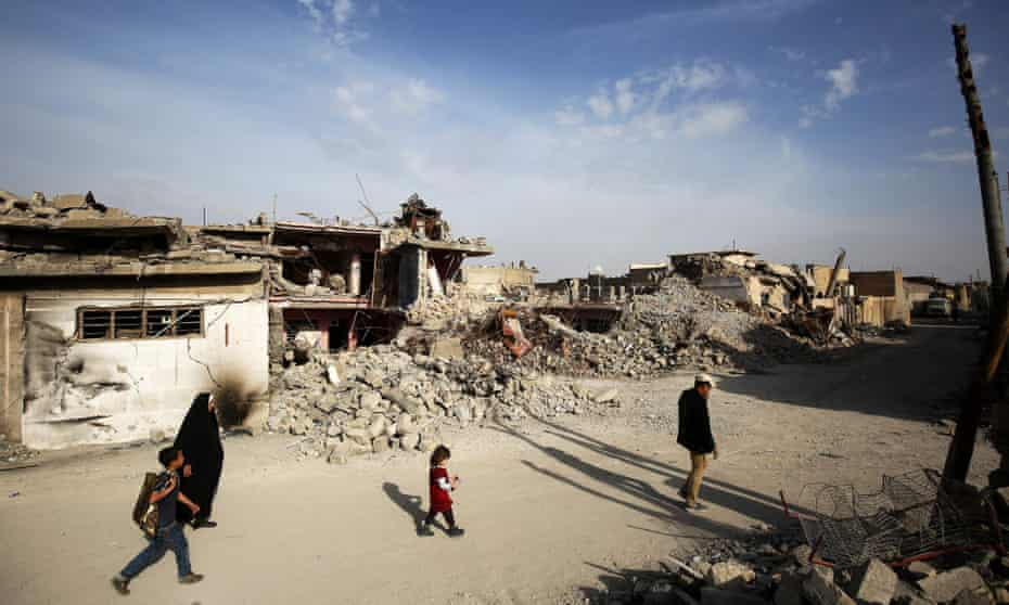 Iraqis walk along a destroyed street in the old city of Mosul eight months after the Iraqi government forces regained control from Isis.