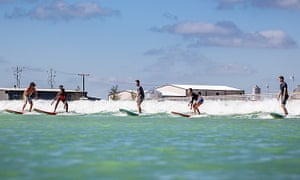 Surfers ride a wave at NLand Surf Park, Austin Texas