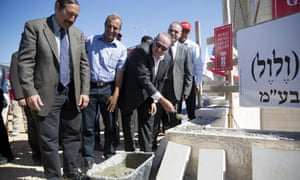 Mike Huckabee lays a brick at a new housing complex in the West Bank settlement of Efrat, on 1 August.