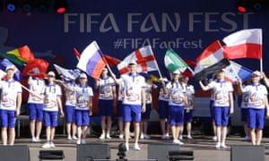 World Cup volunteers wave flags in a designated fan area in Volgograd