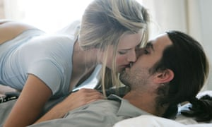 Clothed couple snogging, woman on top