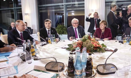 Vladislav Surkov sits next to Vladimir Putin, and two down from Angela Merkel at talks to discuss the situation in Ukraine.
