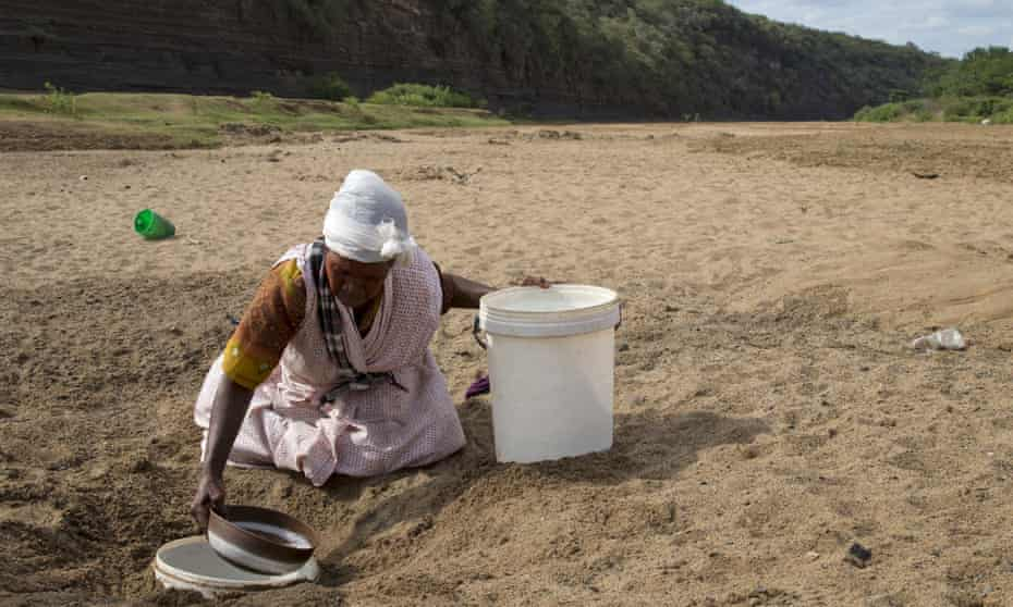 A woman gets water from a well dug in the Black Umfolozi river bed