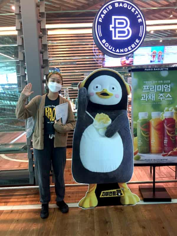 Me at a chain coffee shop in Seoul, next to a promotional Pengsoo cutout.