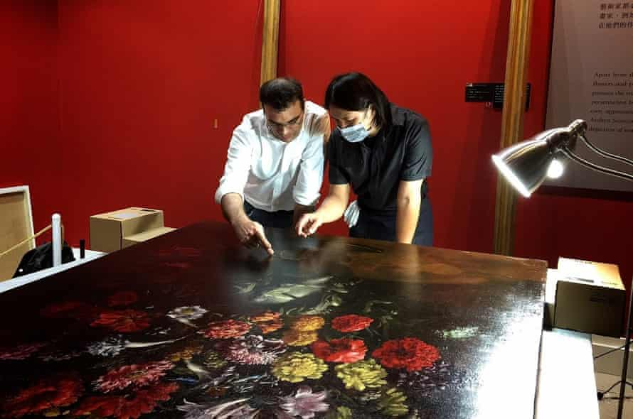 Museum staff and chief conservator Tsai Shun reviewing the damage to the painting in Taipei.