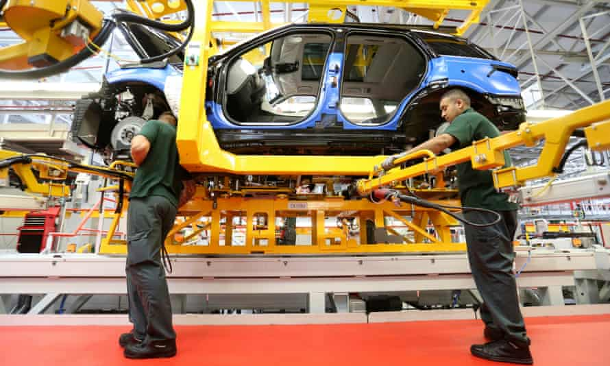 Employees work on a Jaguar Land Rover production line