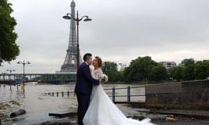 A Chinese couple pose for a wedding photograph on the flooded banks of the Seine.