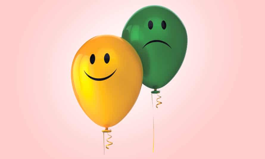 Yellow smiley faced balloon and green sad faced one