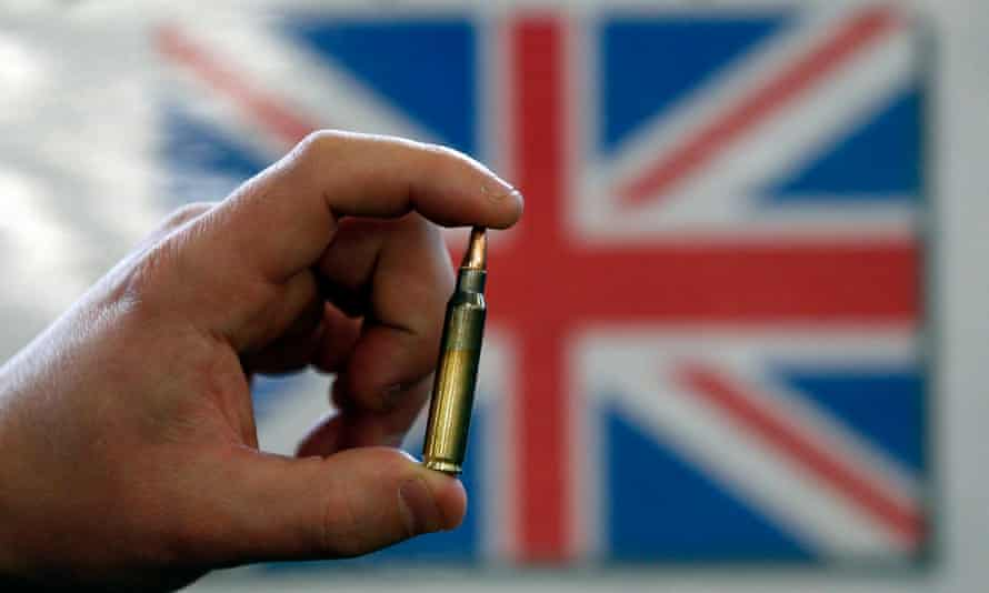 A 5.56mm round is held up in front of a UK flag