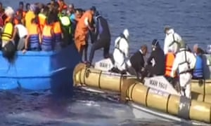 A photograph provided by the Italian navy shows migrants being rescued from the vessel on board which at least 40 died