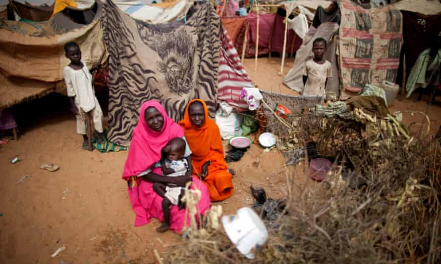 Women and their children sit in a camp in North Darfur. Many of the hundreds deported from Jordan had fled the region.