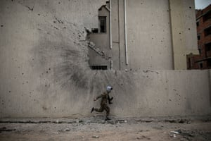 A soldier of the UN-backed Government of National Accord takes cover from Libyan National Army snipers at a frontline in Tripoli.