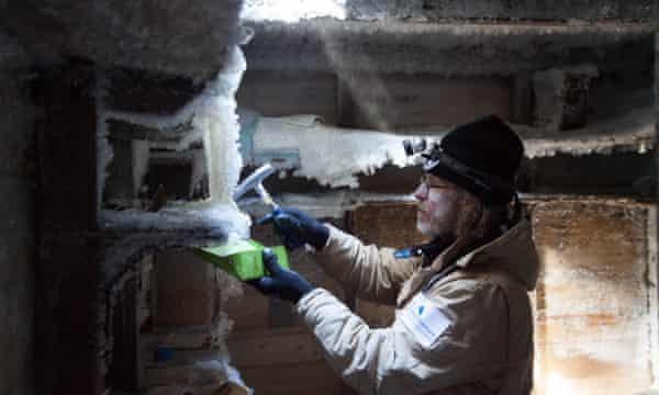 Mawson's Hut Foundation chief conservator Dr Ian Godfrey works to remove ice from shelves inside Mawson's cubicle at Cape Denison, Antarctica.