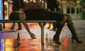 A woman lies on a bench outside a bar in Bristol.