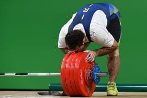 Iran's Sohrab Moradi kisses the weights after winning gold.