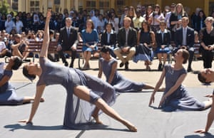 """Britain's Prince Harry, the Duke of Sussex and his wife Meghan, the Duchess of Sussex (behind) watch a dance performance during a visit to Macarthur Girls High School in Sydney, Wednesday, October 19, 2018. In the Royals visit to the school they learned that all year 9 students are currently completing a project where they are investigating issues of social justice and women and youth empowerment including with Australia's National Rugby LeagueÕs (NRL) """"In League In Harmony (ILIH) program"""" which aims to unite and empower young people to be advocates of positive change in their communities. (AAP Image/AFP Pool, Peter Parks) NO ARCHIVING"""