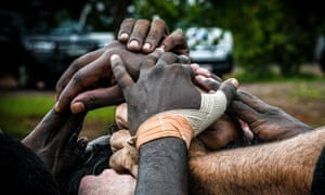 The Tiwi Bombers huddle during the quarter-time break against the Crocs. The white hand of Ashton Hams pokes into the pile, front left