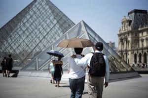Paris, France Visitors shelter under umbrellas at the Louvre museum