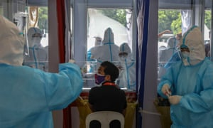 Health workers perform swab tests to government workers in Quezon City, northeast of Manila.