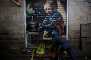 A shop owner in front of shutters decorated with a spray-painted portrait