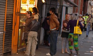 People queuing at a fast food takeaway bar.