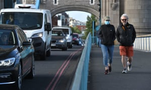 Pedestrians pass heavy traffic on Tower Bridge in London